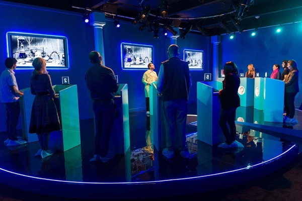 A host plays a scientifically inspired game show with participants placed at 10 podiums